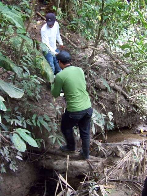 Jimmy lends a helping hand to Andre in crossing a muddy creek and up a slippery slope.