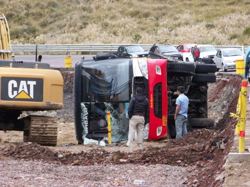 Tour bus flipped off the road into a steep drop-off created by road widening construction.